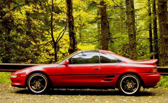 contrasting red MR2 with green natural background