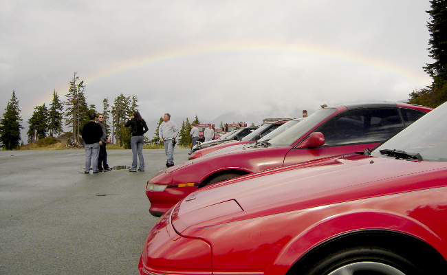 cars in foreground with rainbow in background